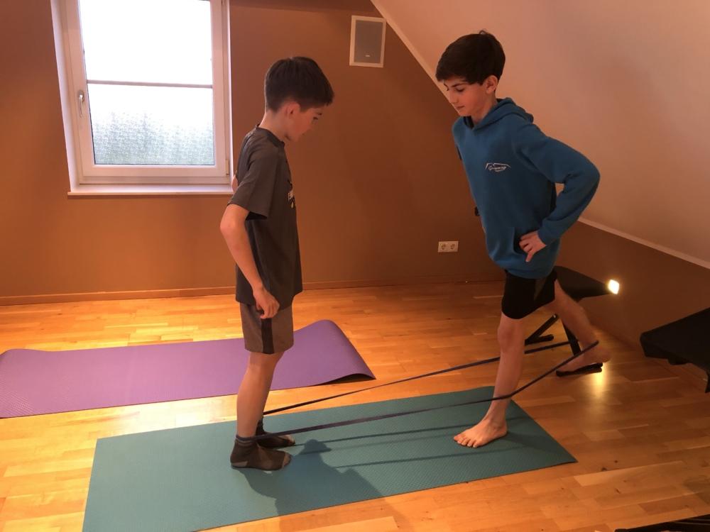 Diese Übung könnt ihr einfach mit jedem Familienmitglied machen. Ihr braucht dazu nur ein längeres Band. Die Bänder könnt ihr einfach bestellen. Einmal geht der eine mit einem Bein nach hinten und dann der andere. Die Übung geht auf beiden Seiten.